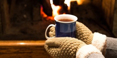 Person wearing mittens holding hot drink in front of fire