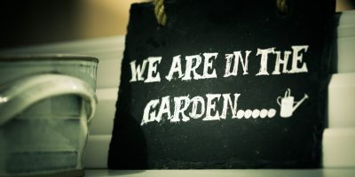 Slate board with 'We are in the Garden...' written on in white paint