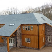 Timber and stone clad house with slate roof tiles