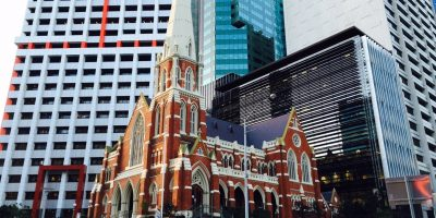 Striking image of church with slate roof tiles surrounded by modern glass buildings in a city